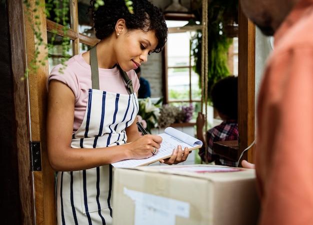 Человек доставляет почтовый ящик женщине перед остановкой