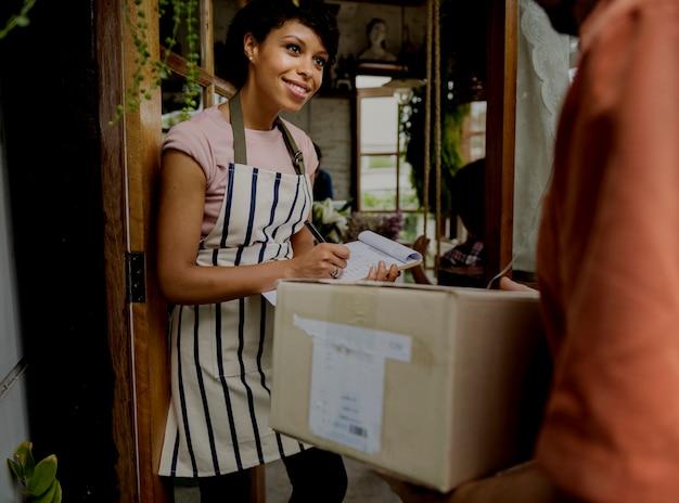 Мужчина доставляет почтовый ящик женщине перед остановкой