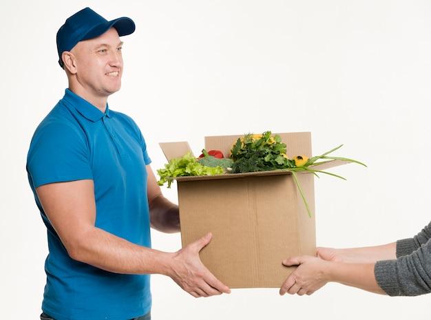 Мужчина доставляет картонную коробку с едой