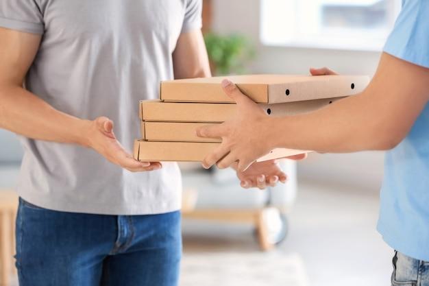 Человек, доставляющий пиццу клиенту в помещении, крупным планом