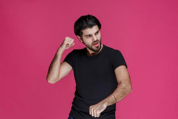 Мужчина демонстрирует свои кулаки и мускулы и показывает, что он силен и удачлив