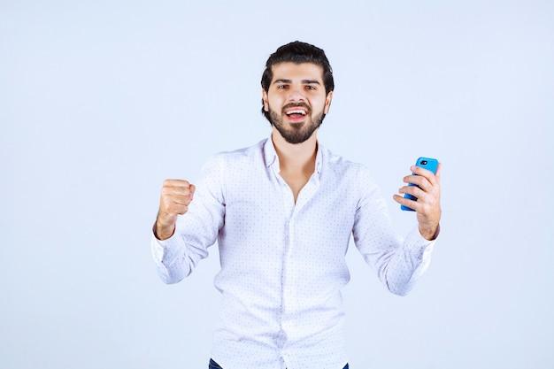 Uomo che mostra il suo nuovo modello di smartphone e si sente soddisfatto