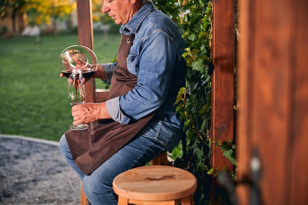 Man in denim clothes wearing an apron in the garden while sitting with a glass decanter and filling it with wine