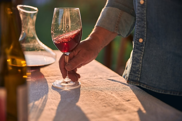 Man in denim shirt touching a glass of red wine with sunlight emerging through it