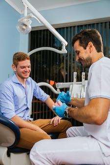 男性の歯科医は、クリニックで彼の患者に歯科手術で入れ歯の歯を見せます。