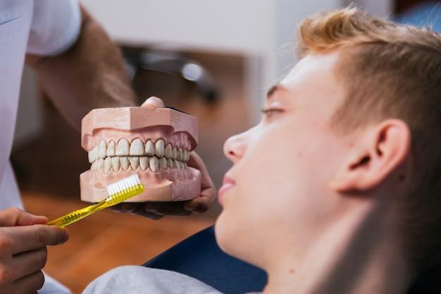 男性歯科医は、クリニックで彼の患者に歯科手術で入れ歯の歯を見せます