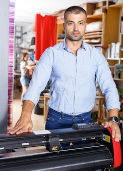 印刷製造でペーパープリントを行う男性デザイナー兼印刷オペレーター Premium写真