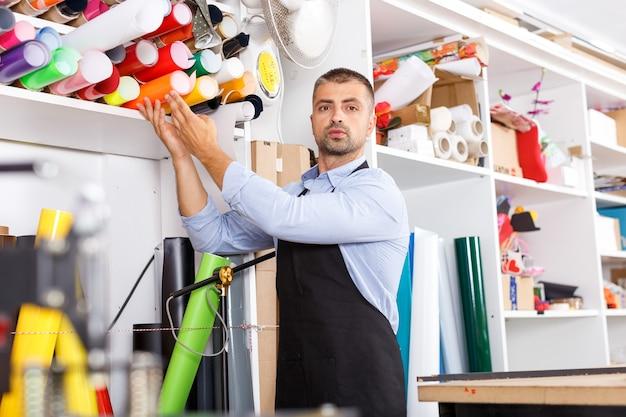 印刷製造でビニール紙を使用する男性デザイナー兼印刷オペレーター