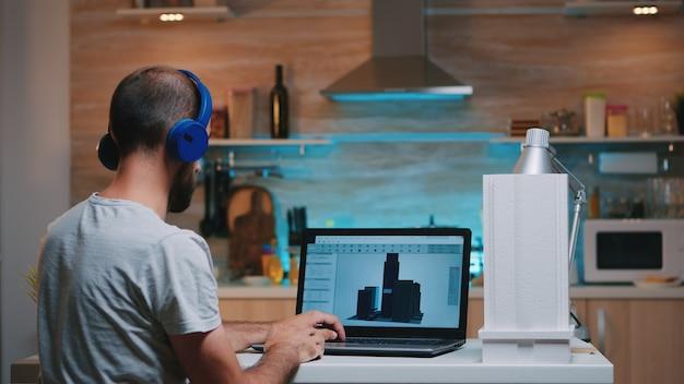 Cadソフトウェアを使用して、自宅から残業している建物の3dコンセプトを設計する男性デザイナー。デバイスのディスプレイを見ているパソコンでプロトタイプのアイデアを勉強している産業男性従業員