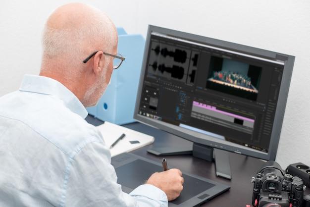 Man designer using graphics tablet for editing