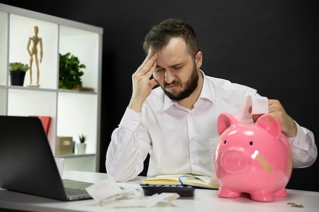 Man in despair looking on bills with broken piggy bank in foreground, bankruptcy
