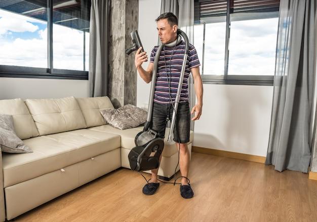 진공 청소기가 거실을 진공 청소기로 청소하는 방법을 이해하려고 필사적으로 노력하는 남자. 전신.