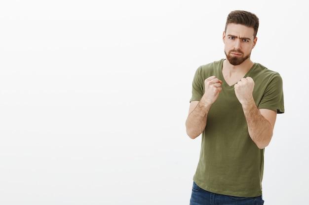 男は休暇後にカロリーと戦うと決心した。パンチとビートの人を望んでいるボクサーのような握りこぶしを握っているので怖い顔をしてtシャツのしかめ面でハンサムな深刻な怒っているひげを生やした男の肖像