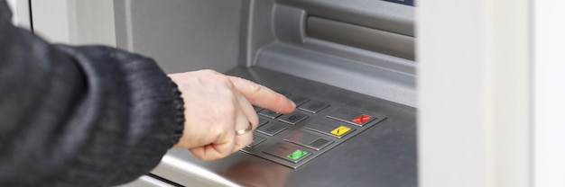 Человек набирает pin-код, чтобы снять деньги в банкомате. человек стоит возле терминала, чтобы снять деньги. оплата товаров и услуг через банкомат. безопасный ввод пароля для снятия наличных