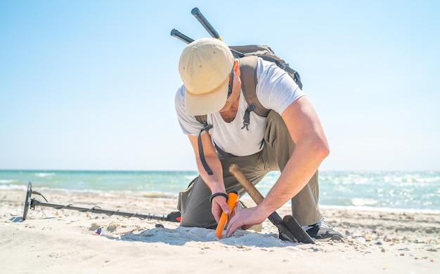 晴れた日に海岸で金属探知機で何かを見つけたときに砂を掘る男。