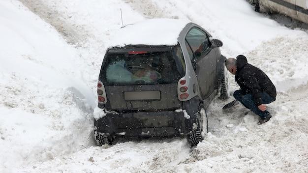 굴착하는 남자가 눈 차에 갇혔습니다. 자동차 바퀴가 눈에 갇혔습니다. 악천후에서 운전. 눈에서 차를 파내는 방법.