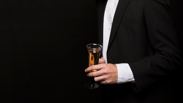 Man in dinner jacket with glass of drink