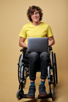 Man disabled student preparing for exam using laptop, sitting on wheelchair isolated in studio. portrait. online education for handicapped people