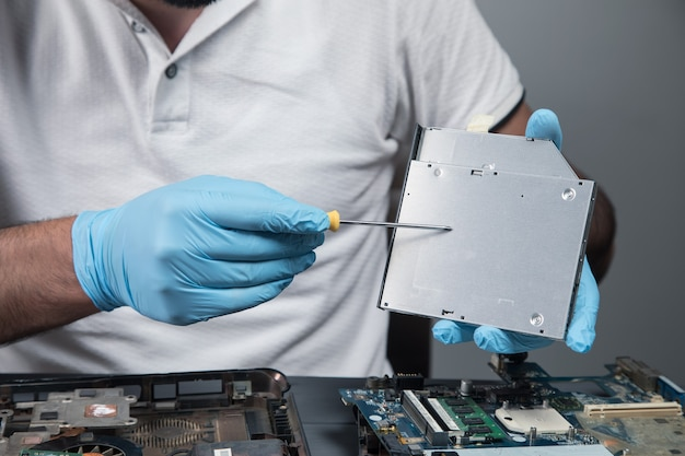 A man disassembles a laptop on a gray wall