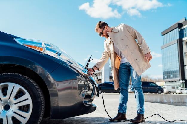 男は電気自動車から充電ケーブルを外します