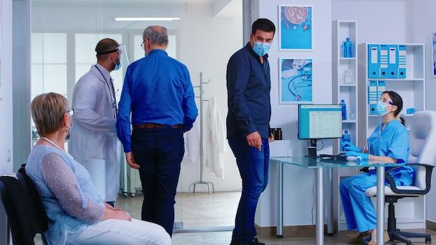 코로나바이러스에 대한 얼굴 마스크를 쓰고 병원 리셉션에서 간호사와 논의하는 남자. covid 전염병 동안 클리닉 검사실에서 의사와 수석 남자. 병원 대기실에 있는 여자.