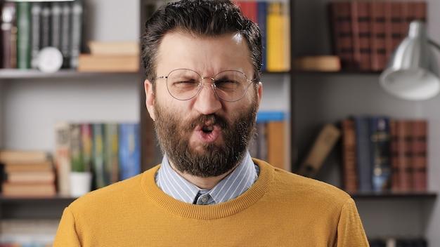 男の嫌悪感、嫌悪感、fu、多くの感情。カメラを見ている眼鏡をかけたひげを生やした男性教師またはビジネスマンと彼の顔は嫌悪感で歪んでいます。ミディアムショット