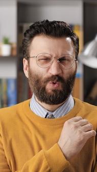 男の嫌悪感、嫌悪感、fu、多くの感情。カメラを見ている眼鏡をかけたひげを生やした男性教師またはビジネスマンの垂直方向のビューと彼の顔は嫌悪感で歪んでいます。ミディアムショット