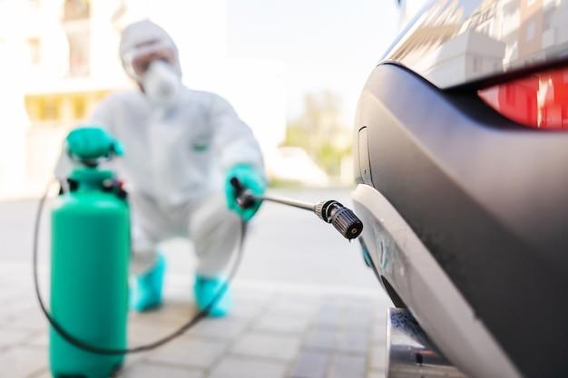 コロナウイルスの間に車を消毒する人。