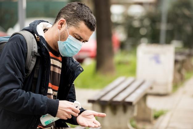 Man disinfecting his hands due to coronavirus risk