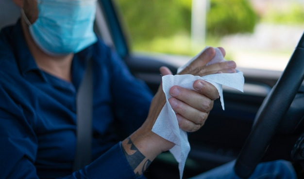Man disinfecting his hands with wipes inside the car
