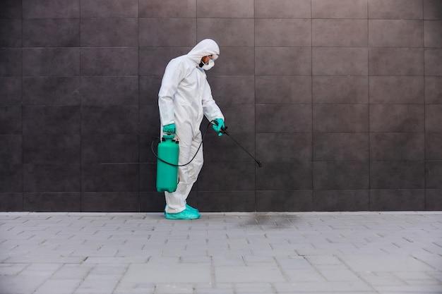 코로나 바이러스 동안 거리를 소독하는 남자.