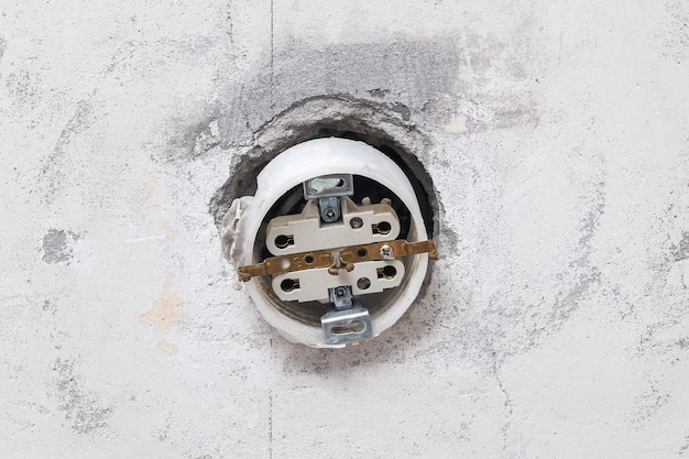 A man dismantles and mends an electrical outlet for repairs