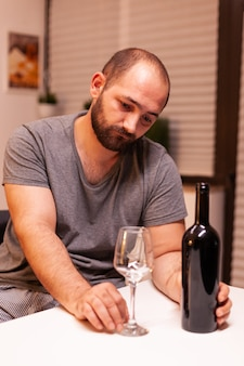 Man in dispair drinking alcohol alone sitting at table in kitchen. unhappy person disease and anxiety feeling exhausted with dizziness symptoms having alcoholism problems.