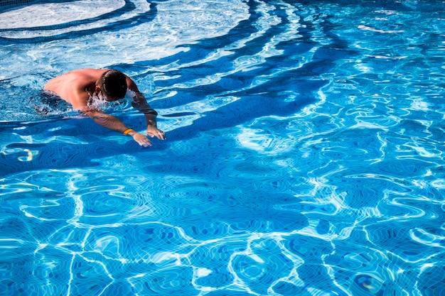 男は青い水でプールに飛び込む