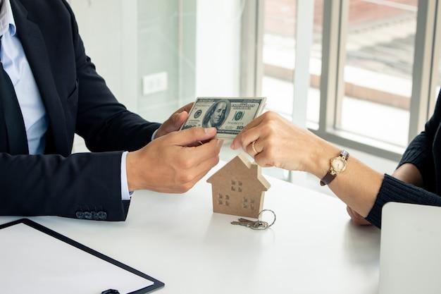 男は請負業者と家を買うためにお金を払う。
