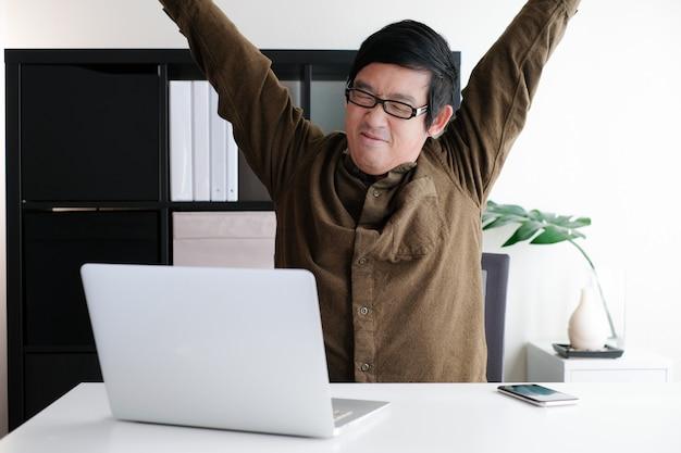 男は携帯電話とコンピューターのラップトップでホームオフィスから仕事をしながらストレッチ体を行います。