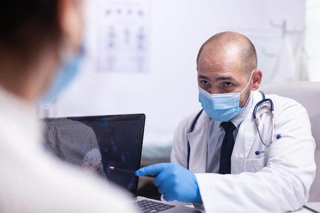 남자 의사와 보호 마스크를 쓴 젊은 환자는 병원 사무실 클리닉의 노트북 앞에 의자에 앉아 바이러스 진화에 대해 이야기합니다. 바탕 화면을 가리키는 증상을 보여주는 의료 종사자
