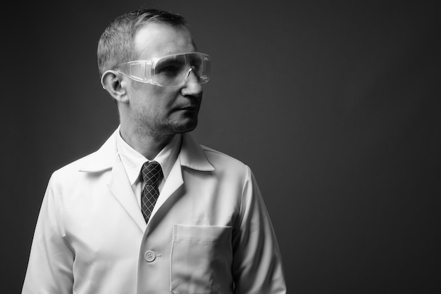 Man doctor as scientist wearing protective glasses against gray wall in black and white