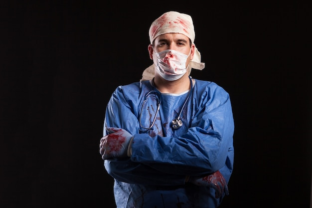 Man in doctor costume for halloween looking with a bizzare face at the camera. weird male with medical costume.