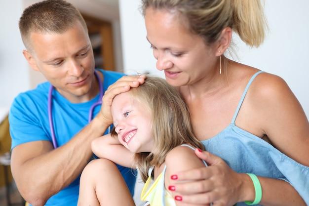 男医師は休暇の概念で母の膝の家族の健康保険に座っている病気の女の子を調べます