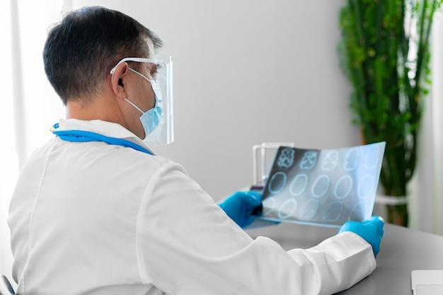 病院のテーブルに座って頭のmriを調べる男性医師のクローズアップ