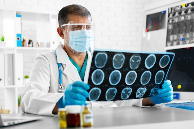 Man doctor examining head mri while sitting at the table in hospital
