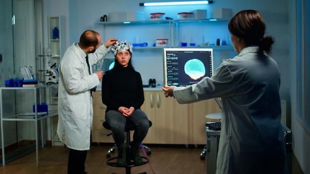 Мужчина-врач изучает датчики eeg-гарнитуры, отслеживает функции мозга, в то время как медицинский исследователь анализирует томографическое сканирование на мониторе, работая в научной неврологической лаборатории