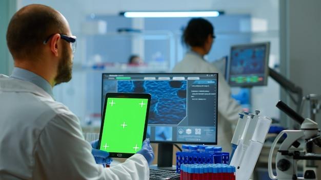 바이러스 진화를 분석하는 현대적인 시설을 갖춘 실험실에서 녹색 화면이 있는 태블릿을 들고 있는 남자 의사. 크로마 키, 격리된 모형 디스플레이가 있는 장치를 보고 백신 연구를 하는 미생물학자 팀