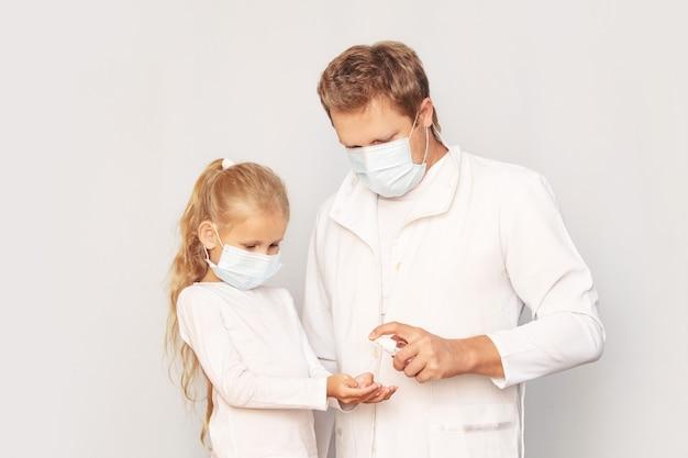 医療用マスクの男性医師は、孤立した背景に抗菌剤で手を消毒する方法を子供に女の子に示します