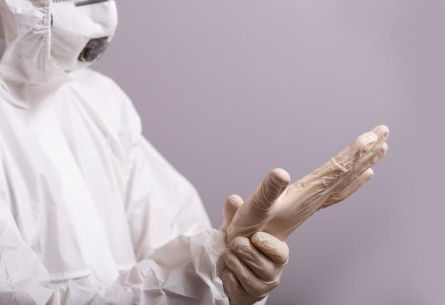 Мужчина, врач в защитном костюме от бактериальной и вирусной инфекции, 19 лет, носит резиновые перчатки для защиты. остановись, оставайся дома.