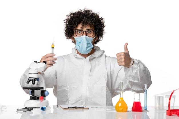 防護服と白の注射を保持しているマスクの男性医師