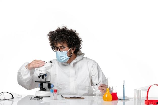 白の顕微鏡を使用して、防護服とマスクを着た男性医師