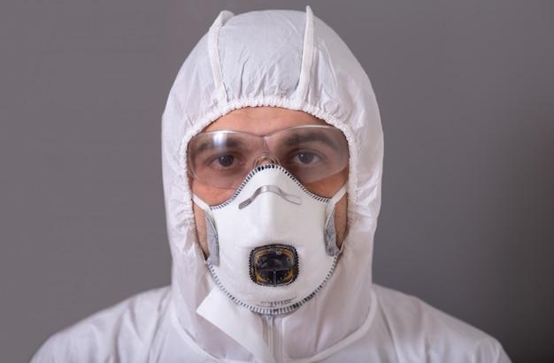 Мужчина, врач в защитном костюме, маске, очках и перчатках от бактериальной и вирусной инфекции, 19 лет, во время пандемии устал, измотан, остановился, остался дома.