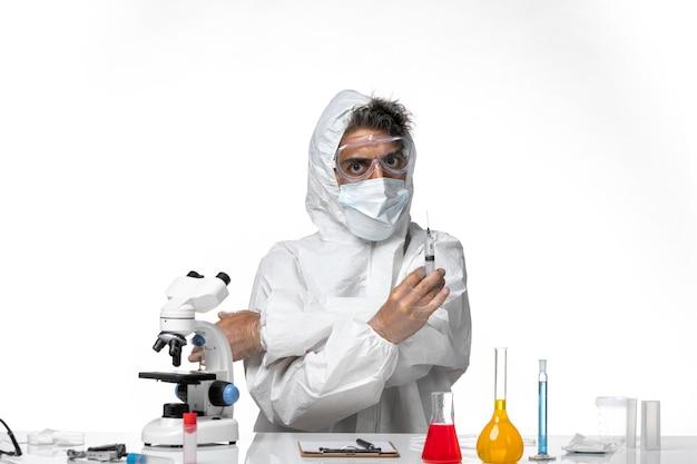 Человек-врач в защитном костюме со стерильной маской, держа инъекцию на белом